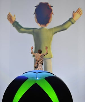 rear view of man standing on giant xbox logo balloon in front of vast cartoon image of himself