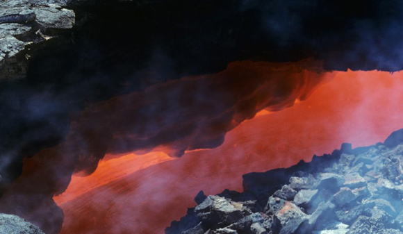 View down a skylight revealing magma racing through a lava tube in Hawaii. Credit: Mark Robinson