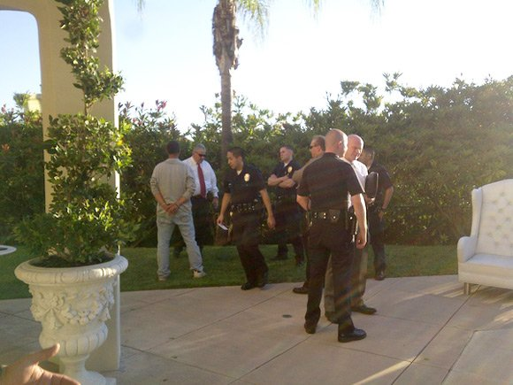 Photo of police and cuffed intruder at Paris Hilton's home