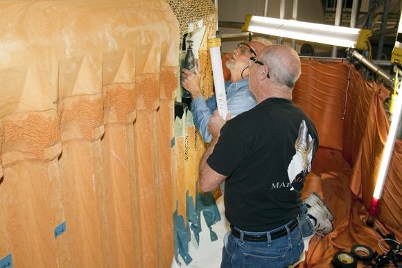 Engineers repairing Discovery's external fuel tank. Pic: NASA