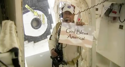 Closeout crew member before the Atlantis launch with sign reading God Bless America. Pic: NASA TV