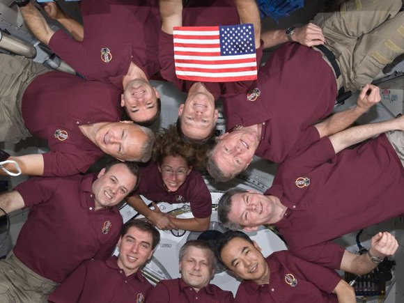 The Atlantis and ISS crew members pose with US flag. Pic: NASA