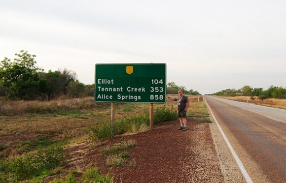 Lester by a Stuart Highway sign showing the distance to Alice Springs