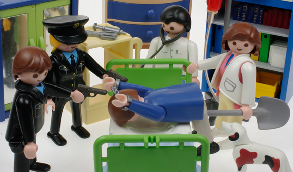 Our traveller is spread over a bed while a nurse extracts a shovel from his backside