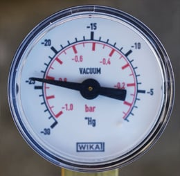 The vacuum gauge indicating 0.15 bar pressure