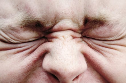 Man wrinkles his eyes in an expression of pain, annoyance or dsicomfort