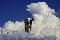 workman in high vis jacket bent over, super-imposed on cloud background