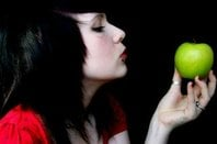 Punk-styled girl with piercing gazes at an apple