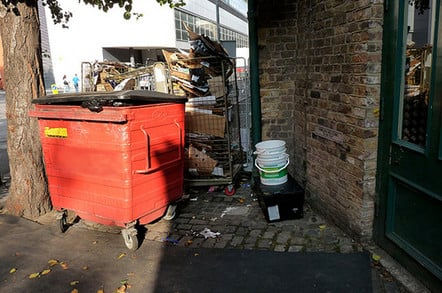 big red wheelie bin and pallet full of rubbish in London street