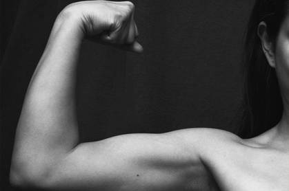 woman's arm flexing biceps