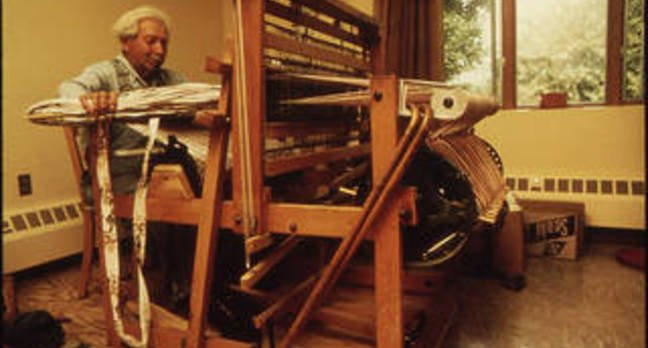Old man sitting at a loom
