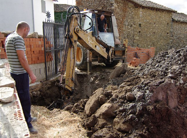 Rui contemplates a big hole next to an enormous pile of earth, as Ramon continues to dig