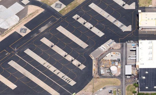 A wide aerial view of an airfield with black helicopters