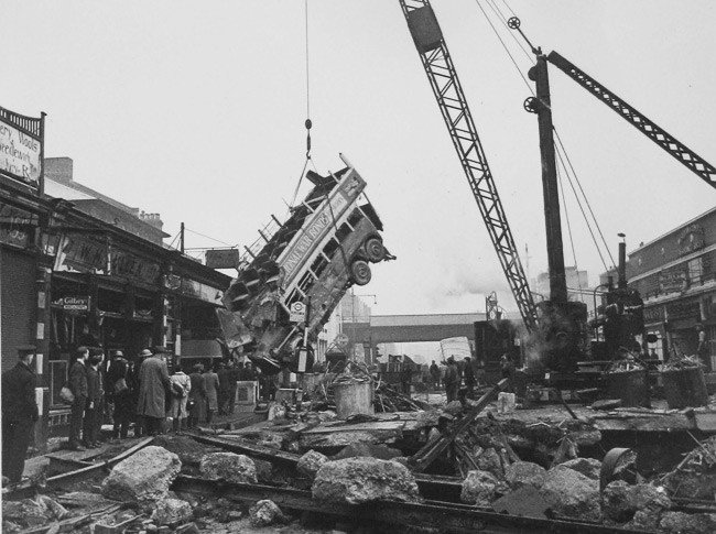 A bus being lifted by crane from the crater above Balham tube station