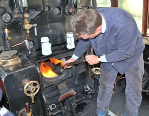 Man stoking boiler in steam engine cab
