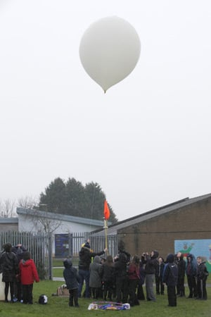 One mission balloon ready for lift-off, as the schoolkids gather round