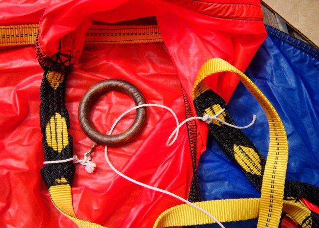 The igniter line attached to the parachute canopy, and passing through a wooden ring on the opposite side