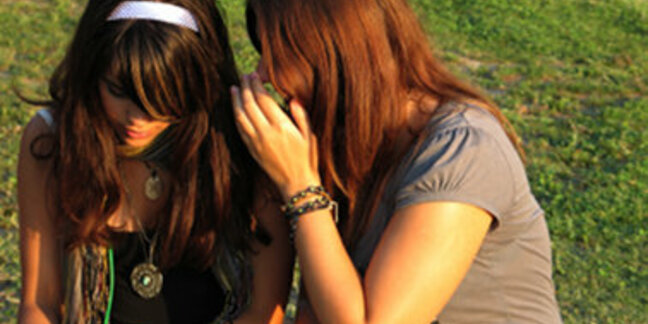 Two teenage girls - one whispering in other's ear