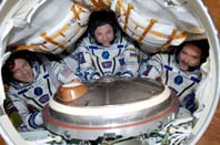 Tom Marshburn (L), Roman Romanenko (C) and Chris Hadfield (R) squeeze into a Russian Soyuz-TMA capsule shortly before their return to Earth.