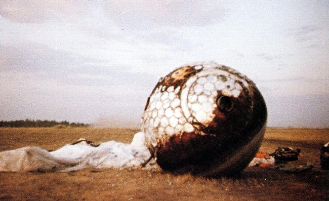The Vostok 3KA-3 is seen with charring and its parachute on the ground after landing south west of Engels, in the Saratov region of southern Russia.