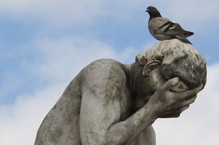 Pigeon crapping on statue