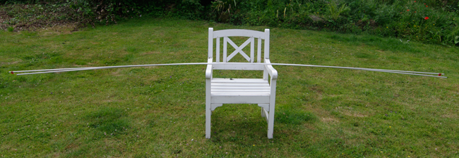 The aluminium tube and bar laid over a chair, showing the degree of bend