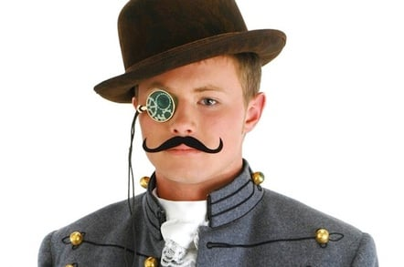 Boy in steampunk fancy dress, with hat, mechanical monocle, waxed moustache, cravat and Bavarian-type jacket