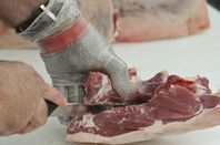 hand in chain mail glove cutting meat with sharp knife