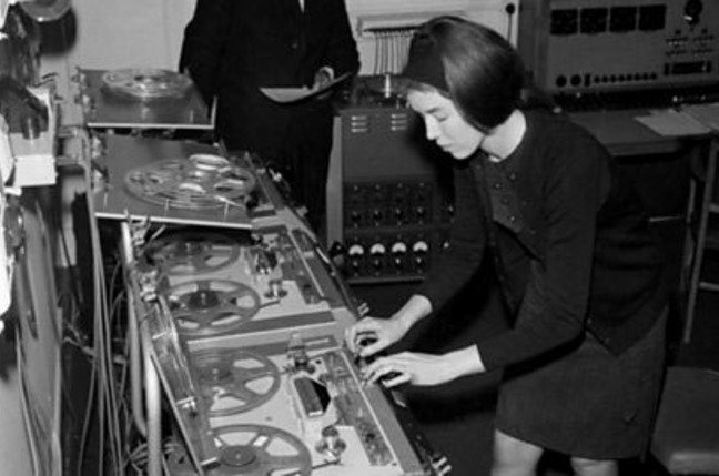 Delia Derbyshire edits on a Philips EL3503 while Desmond Briscoe checks the script
