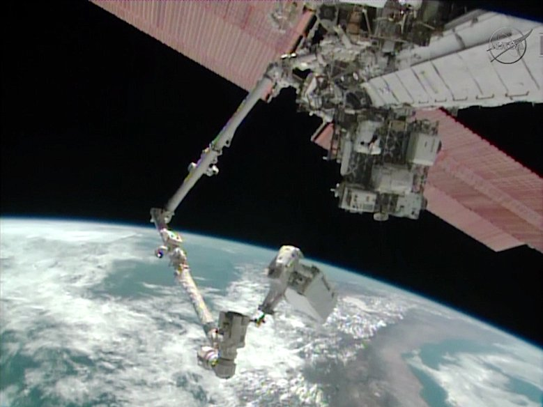 Astronaut Mike Hopkins rides the Canadarm2 carrying the 780-pound ammonia pump module as the International Space Station flies over South America