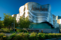 Neiman Marcus Massachusetts HQ: pearlescent gold and silver building surrounded by lush plants against a blue sky.