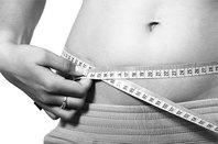 A person measuring her waistline