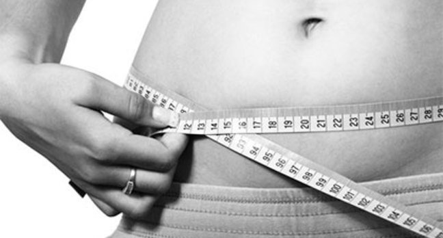 A person measuring her waistline