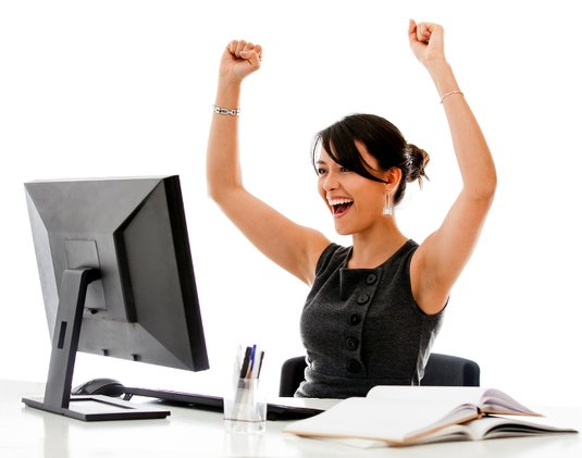 Woman looks immensely happy while staring into blank screen of unplugged monitor