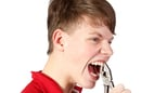 Youth gripping his front teeth with a pair of pliers