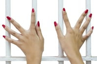 Female hands behind cell bars
