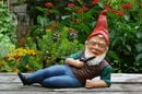 A garden gnome depicted stretched out across picnic table... with a pipe in one hand while the other props him up. Has a confrontational look in his eye...