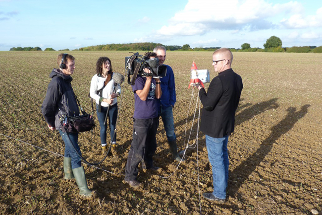 Blumenthal and film crew in a field with the landed payload