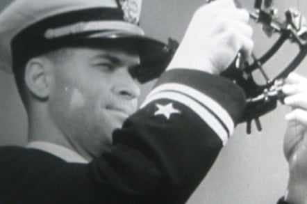 An officer of the U.S. Navy uses a sextant to determine his position.