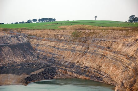 The northern end of the huge water-filled pit, showing the coal seams in the rock at Broken Cross Muir opencast coal mine