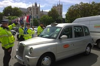 Police direct a cabbie at the Uber protest in London