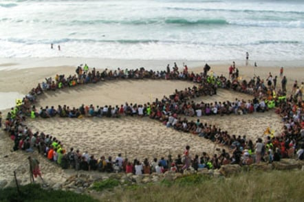 Hippies stage sitdown on beach (in shape of peace sign)