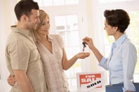 An estate agent hands keys to a couple after house sale. Photo by Shutterstock