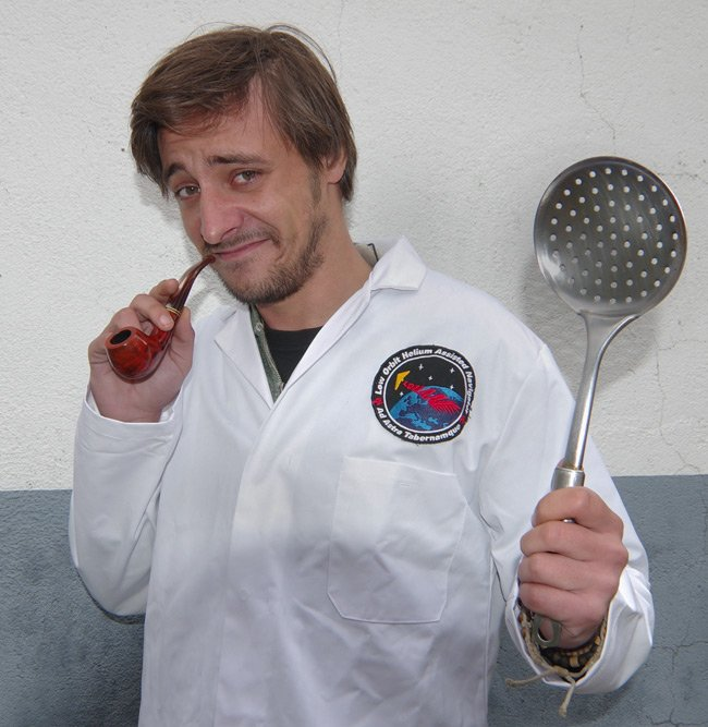 Matthew Haines poses with lab coat, pipe and kitchen implement