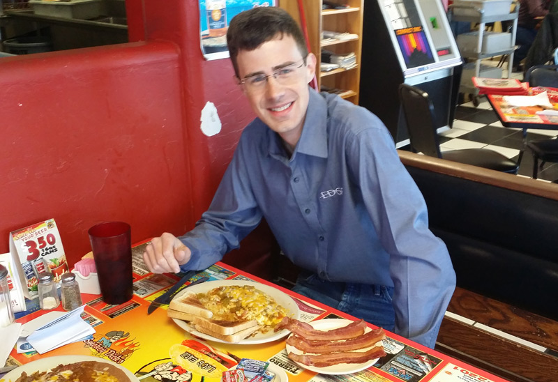 David Patterson about to tuck into breakfast, with a side of bacon