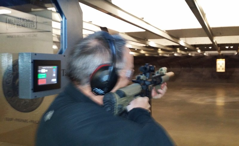 Lester firing an AR-15 at the gun range