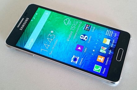The SAMSUNG GALAXY ALPHA lies on a white background, displays Home screen icons.