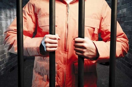 Man in an orange jumpsuit clutches prison bars. Image by Shutterstock