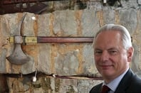Cabinet Office minister Francis Maude against bakdrop of '70s stone facade with old axes hung up on wall (background by Michael Coghlan, licensed under CC 2.0