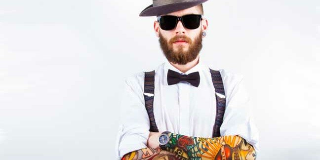 Young hipster man wearing hat, suspenders, bow-tie and fake-looking tattoo-sleeve. Image via shutterstock